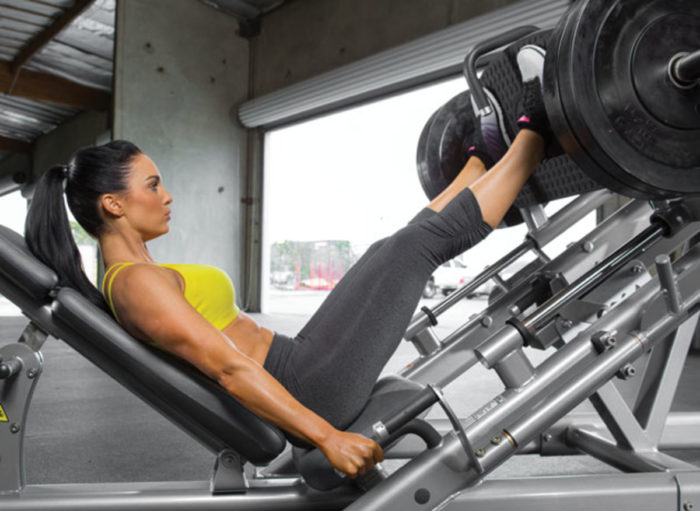 woman performing a leg press in the gym